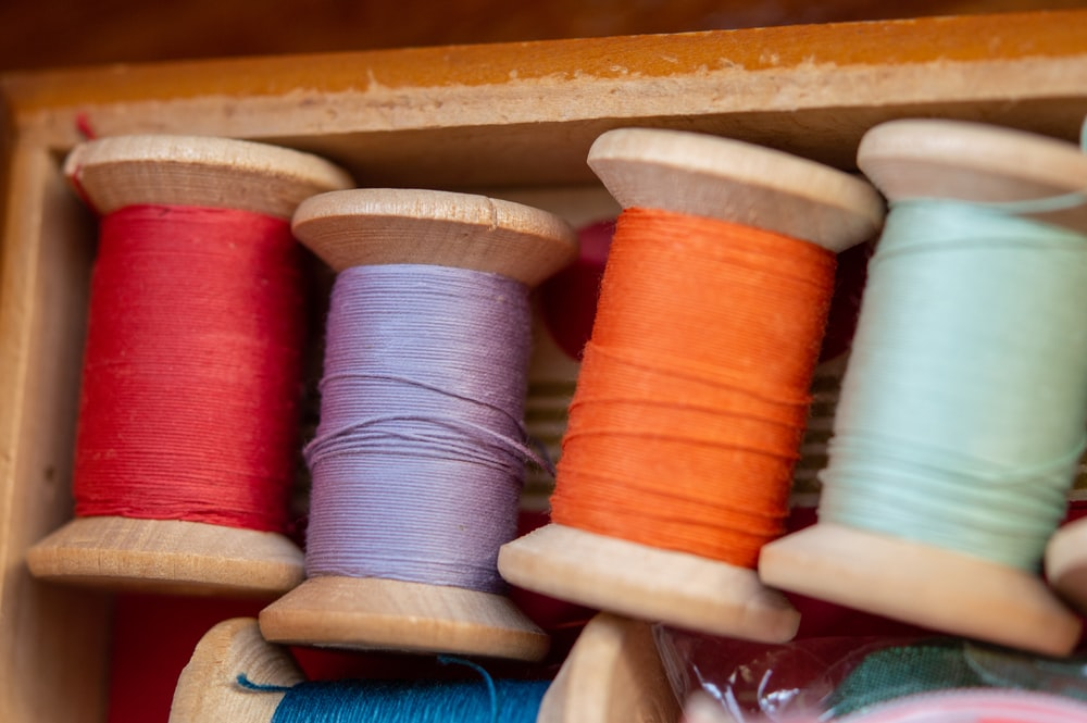 blue and red thread on brown wooden rack