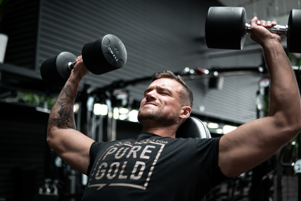 man in black crew neck t-shirt holding black and silver dumbbell