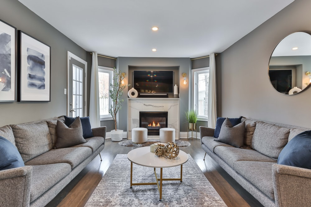 gray couch near white fireplace