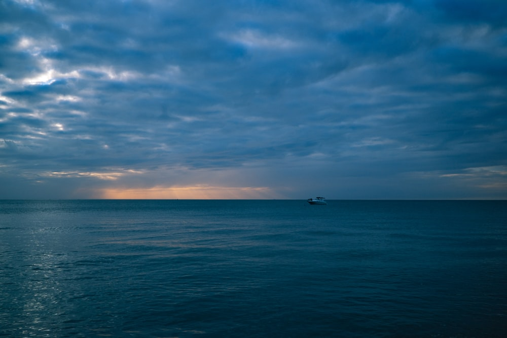 boat on sea under blue sky and white clouds during daytime