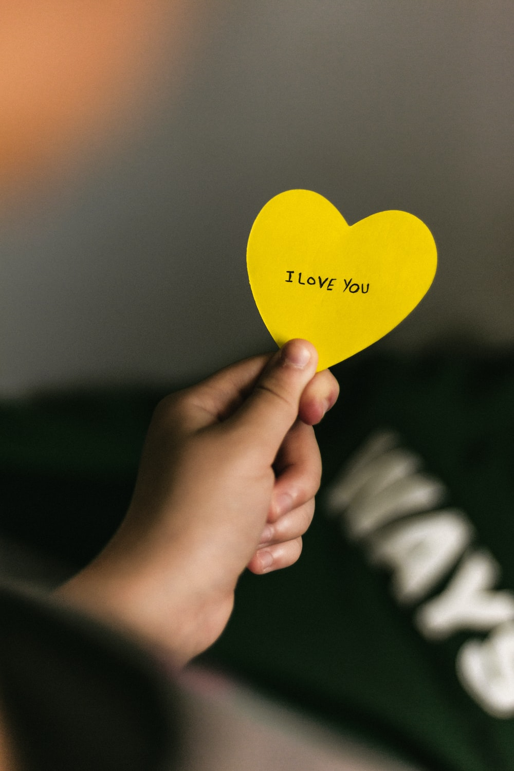 person holding yellow heart paper