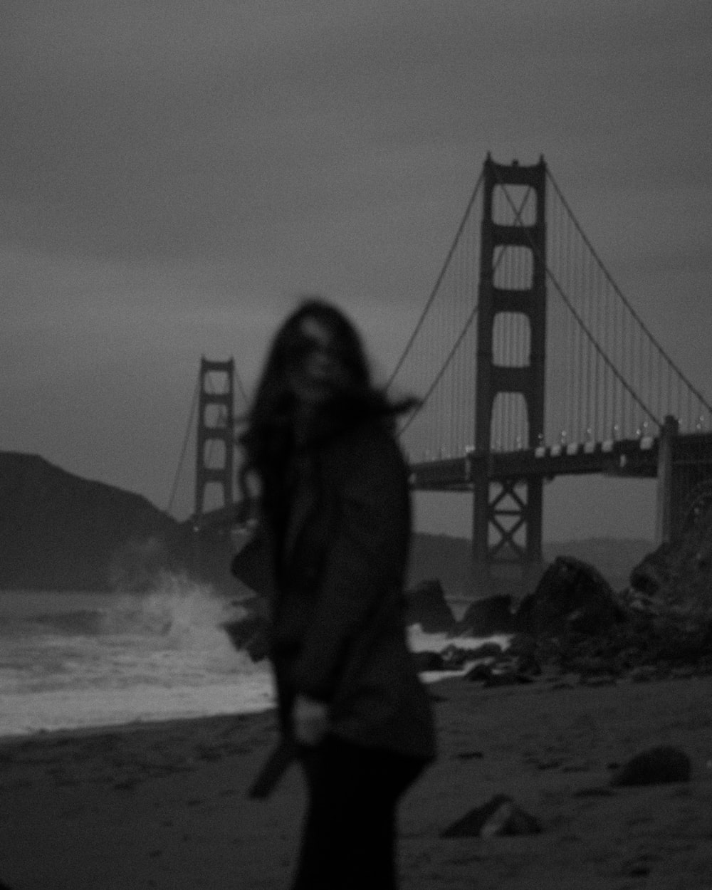woman in jacket standing on beach near golden gate bridge in grayscale photography