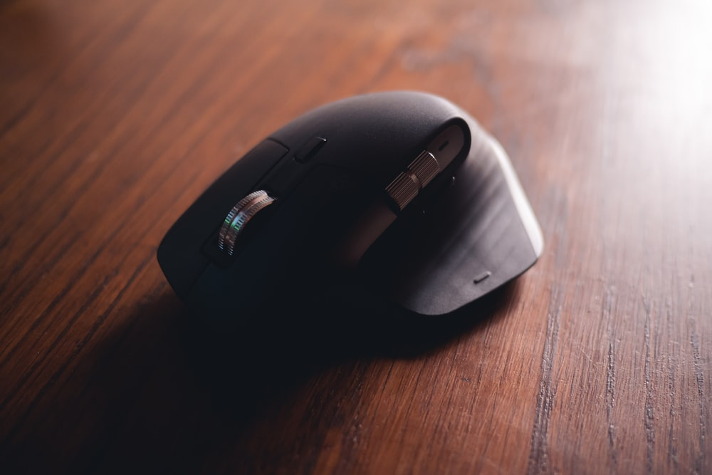 black cordless computer mouse on brown wooden table