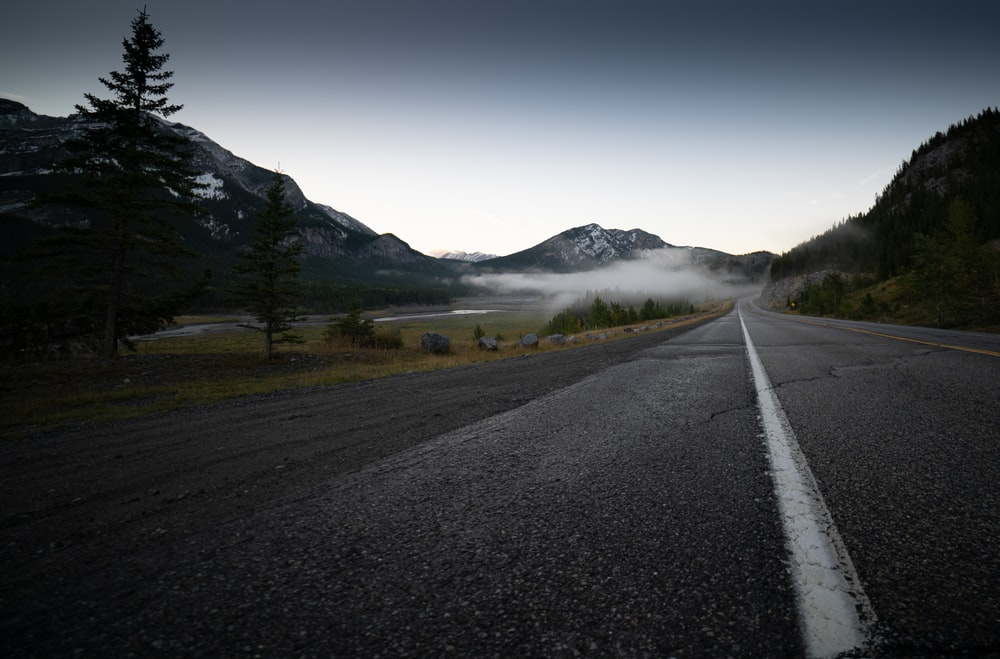 gray asphalt road near green grass field and mountain during daytime