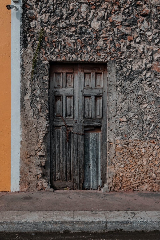 black wooden door on orange concrete wall
