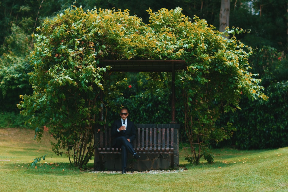 man in black jacket sitting on black wooden bench