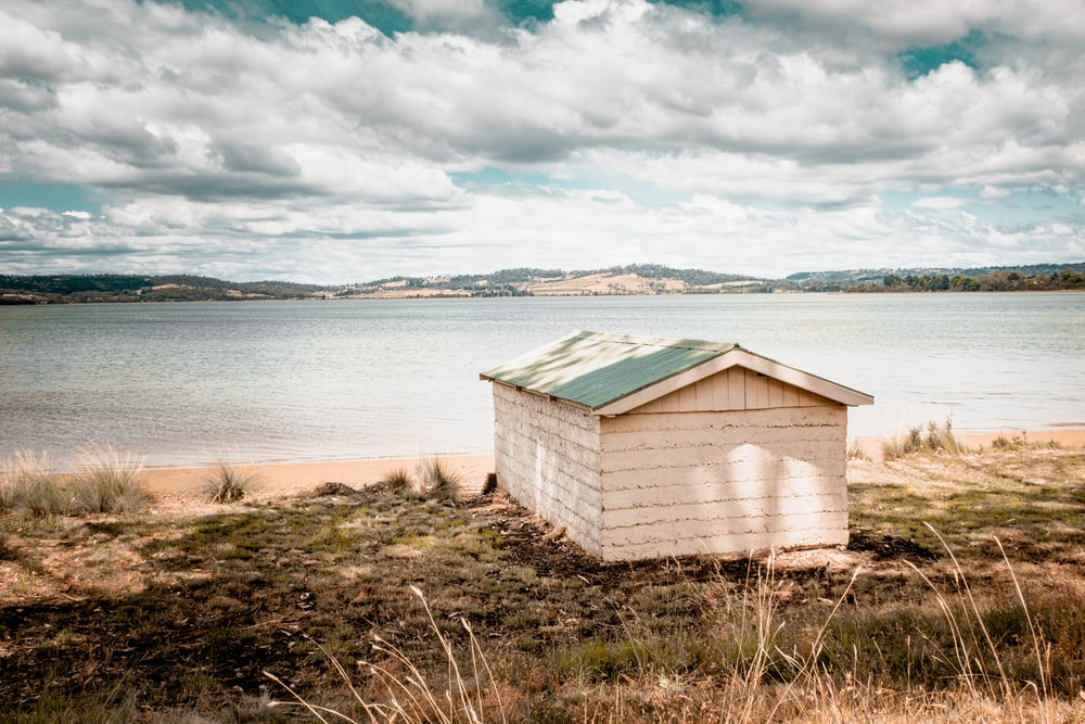 brown wooden house near body of water under white clouds during daytime