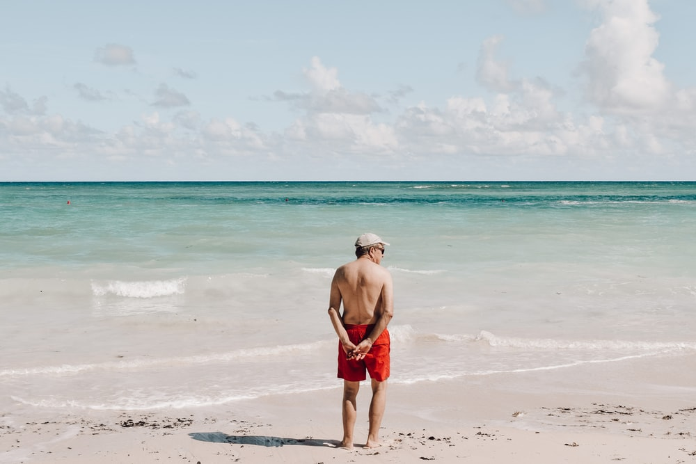 man in red shorts standing on beach during daytime