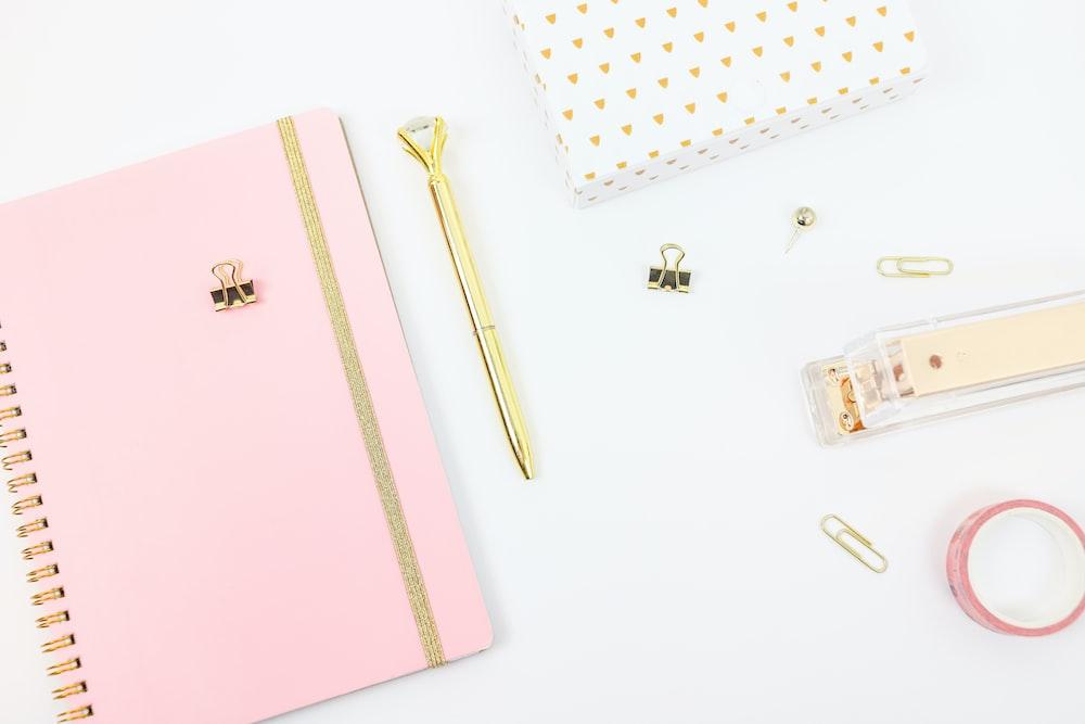 gold pen beside pink book