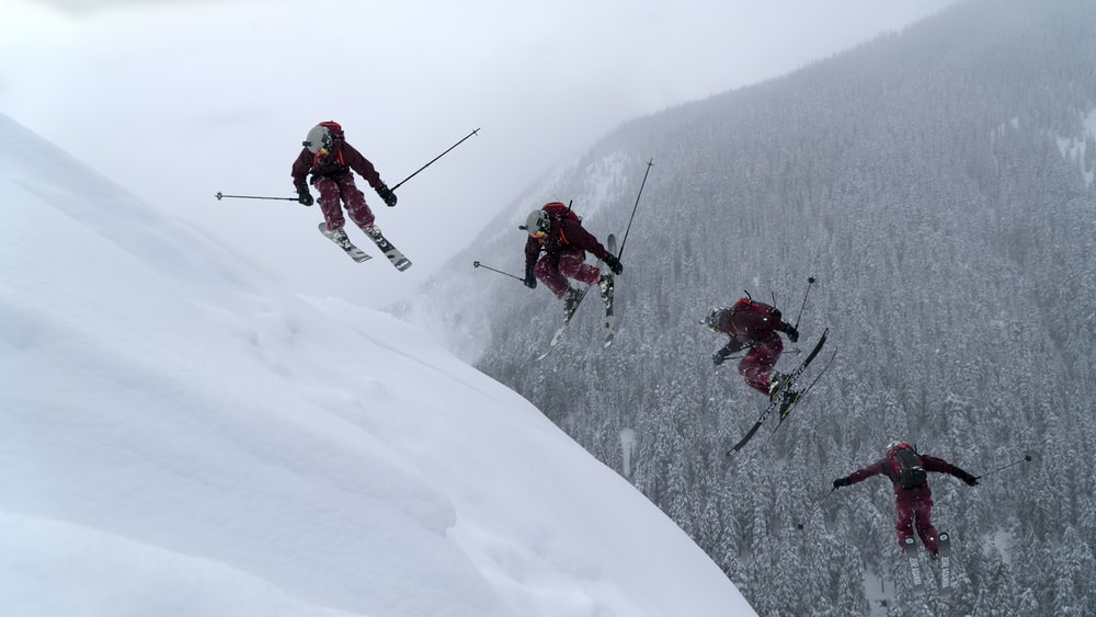 people in red jacket and black pants riding ski blades on snow covered mountain during daytime
