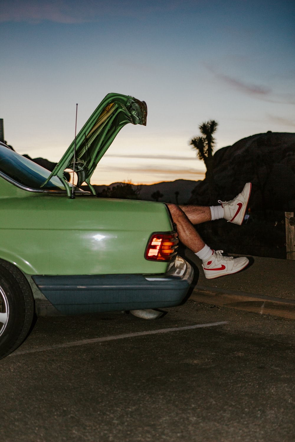 person in black and white nike sneakers sitting on green car hood during daytime
