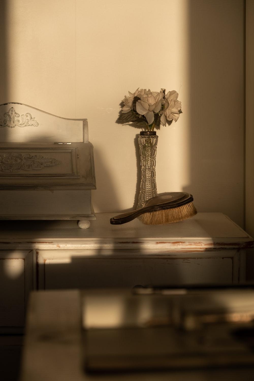 white flower in vase beside brown wooden hair brush
