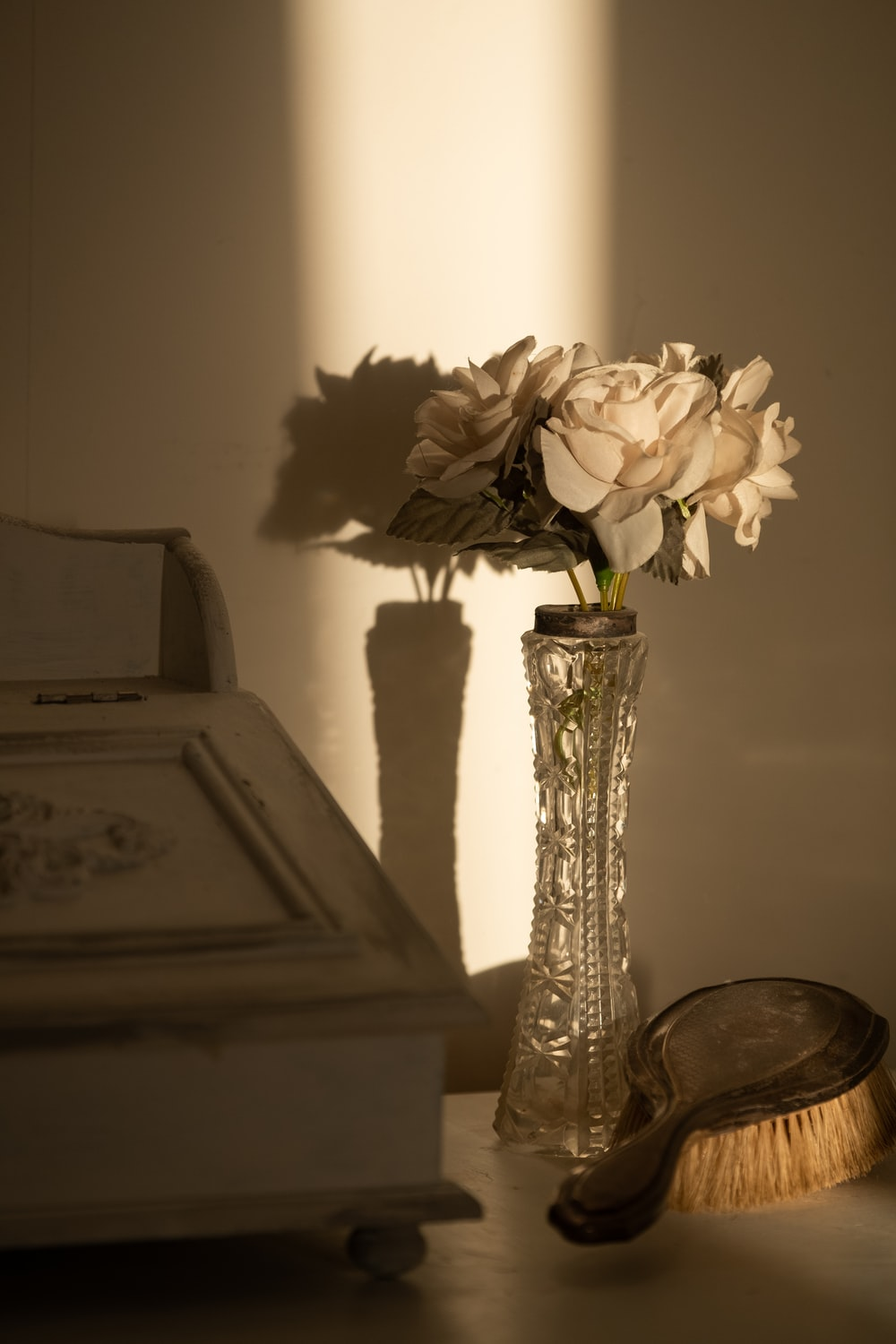 white flower in clear glass vase on brown wooden table