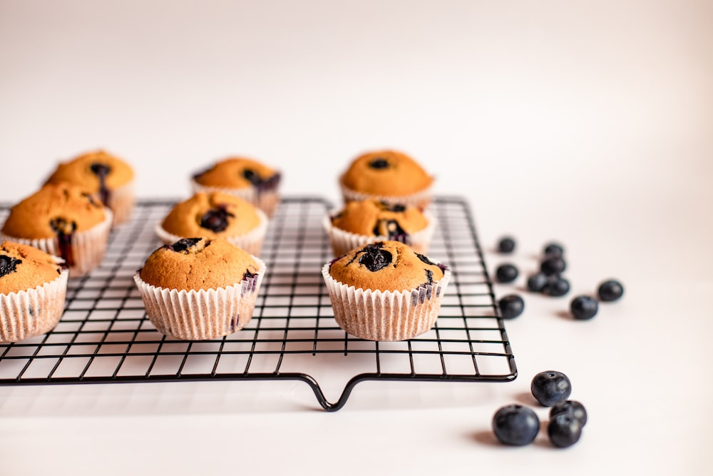 three brown and black cupcakes on white tray