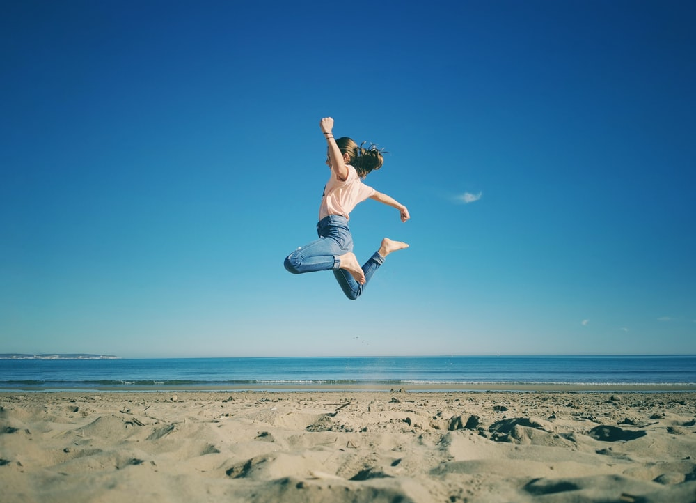 woman in white tank top and blue denim shorts jumping on beach during daytime