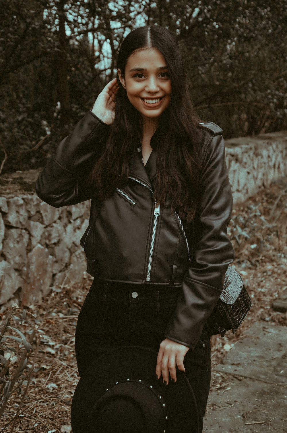 woman in black leather jacket standing near brown dried leaves during daytime