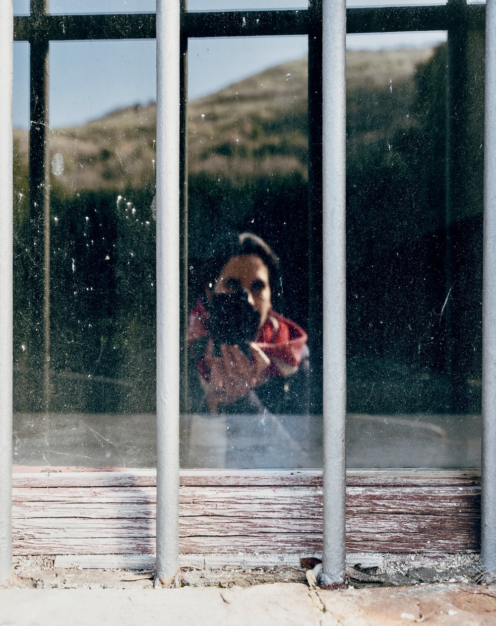 girl in red and white jacket standing beside window