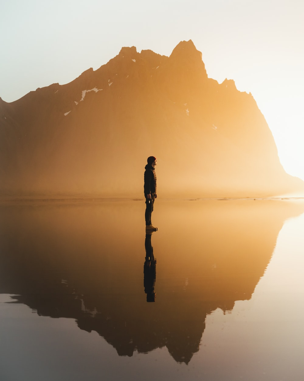 silhouette of woman standing on water during daytime