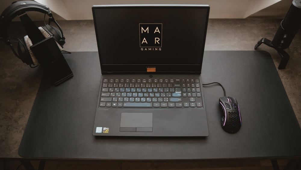black asus laptop computer on black table