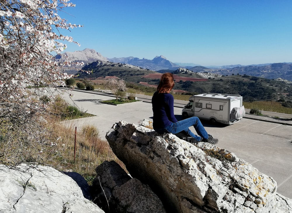 woman in black long sleeve shirt sitting on rock near body of water during daytime