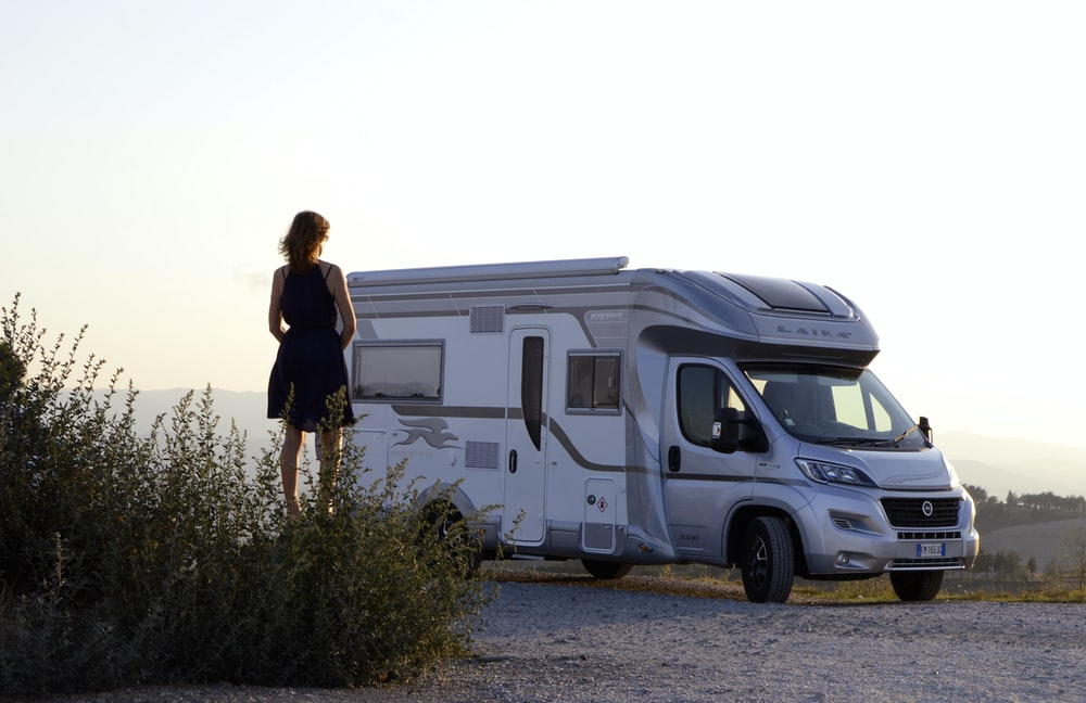 woman in black dress standing beside white and blue rv trailer during daytime