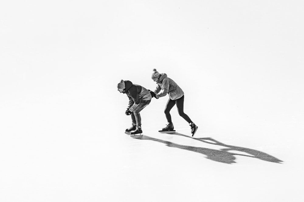 2 men playing skateboard on white snow covered ground