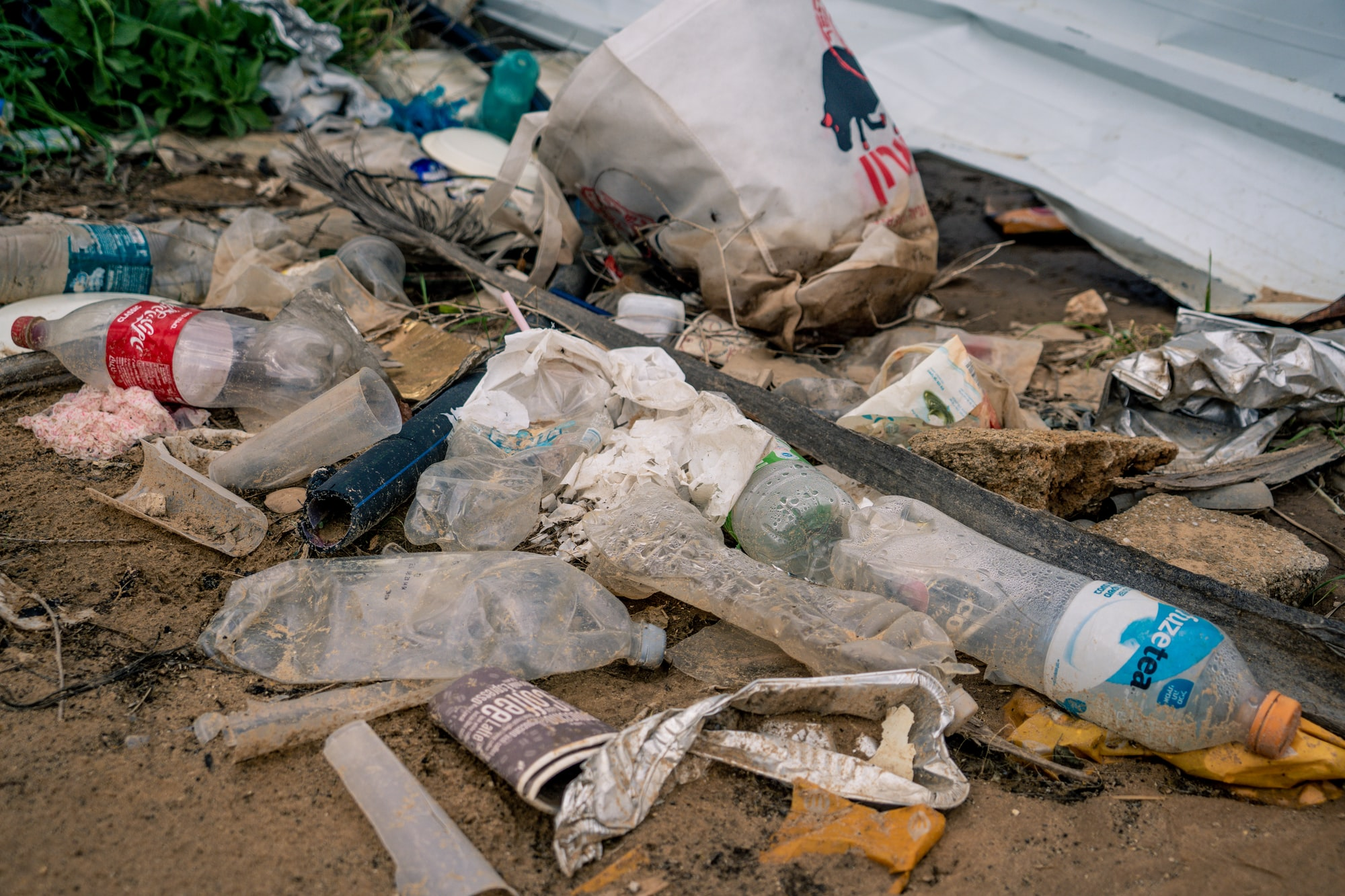dump of dirty garbage near the road: empty plastic bottles, disposable cups, bags