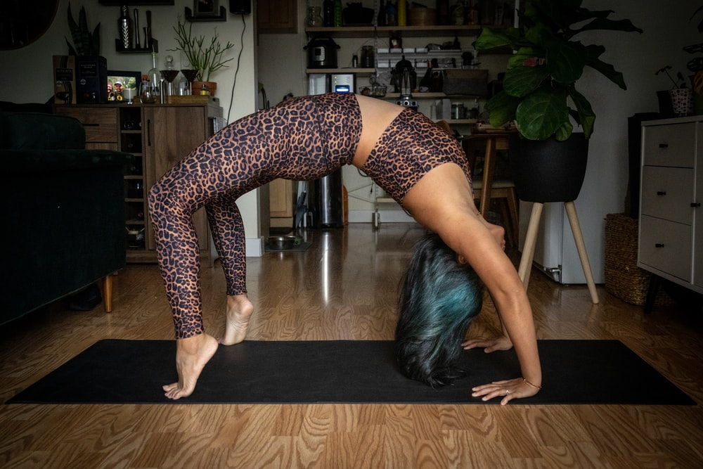 woman in black and white polka dots leggings bending her body on brown wooden table