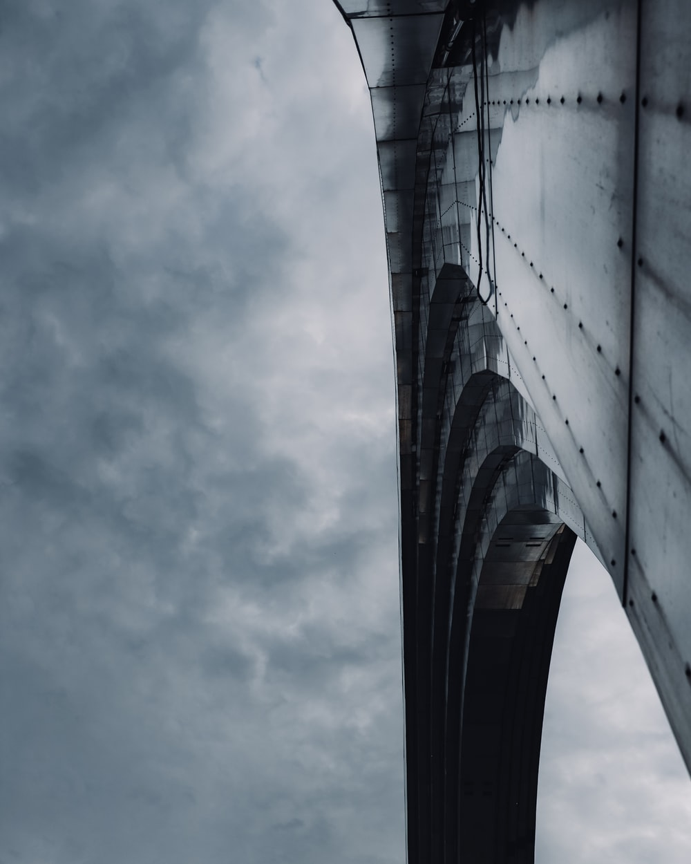 low angle photography of bridge under cloudy sky during daytime