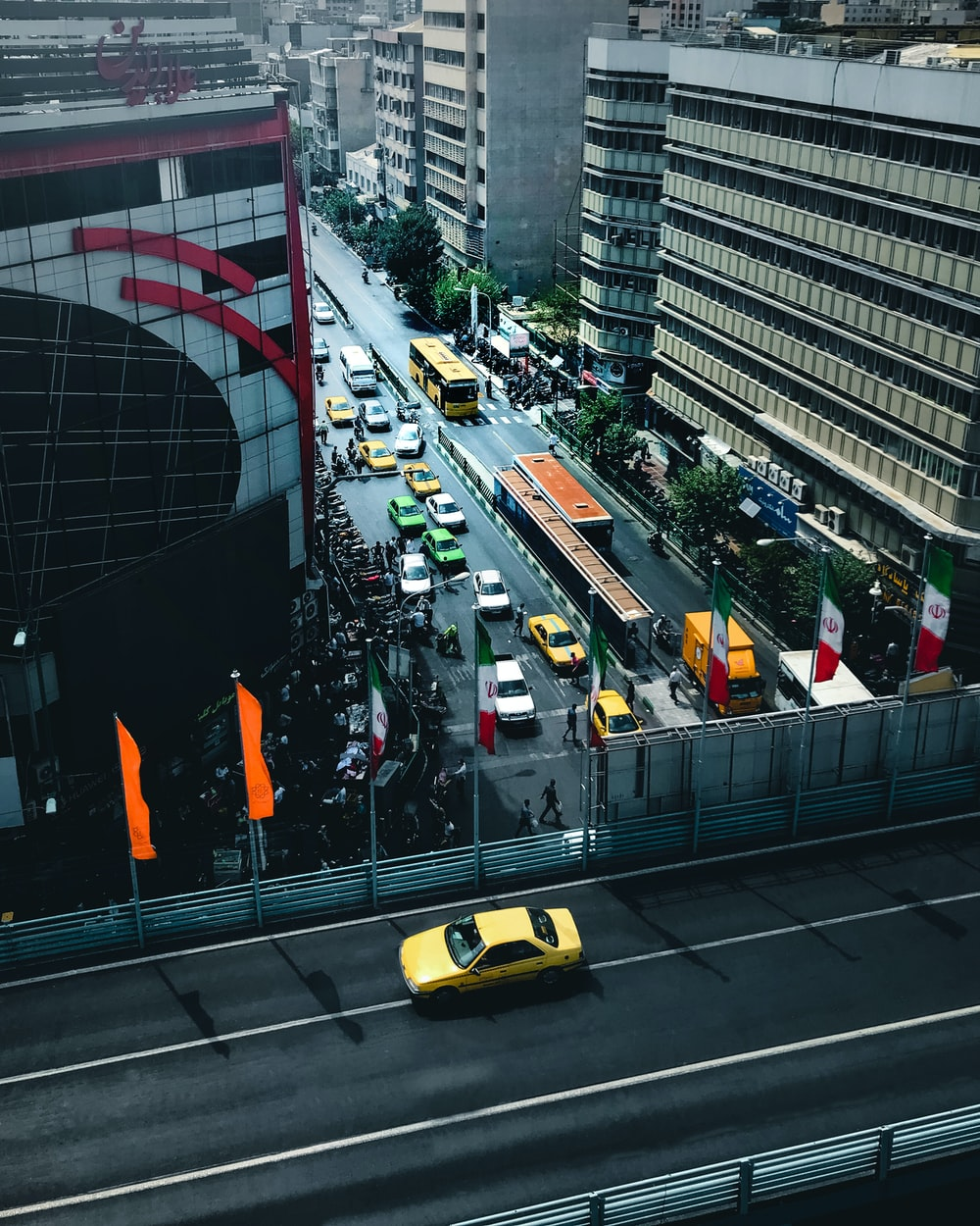 yellow taxi on road near high rise buildings during daytime