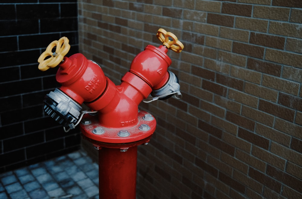 red fire hydrant near brown brick wall