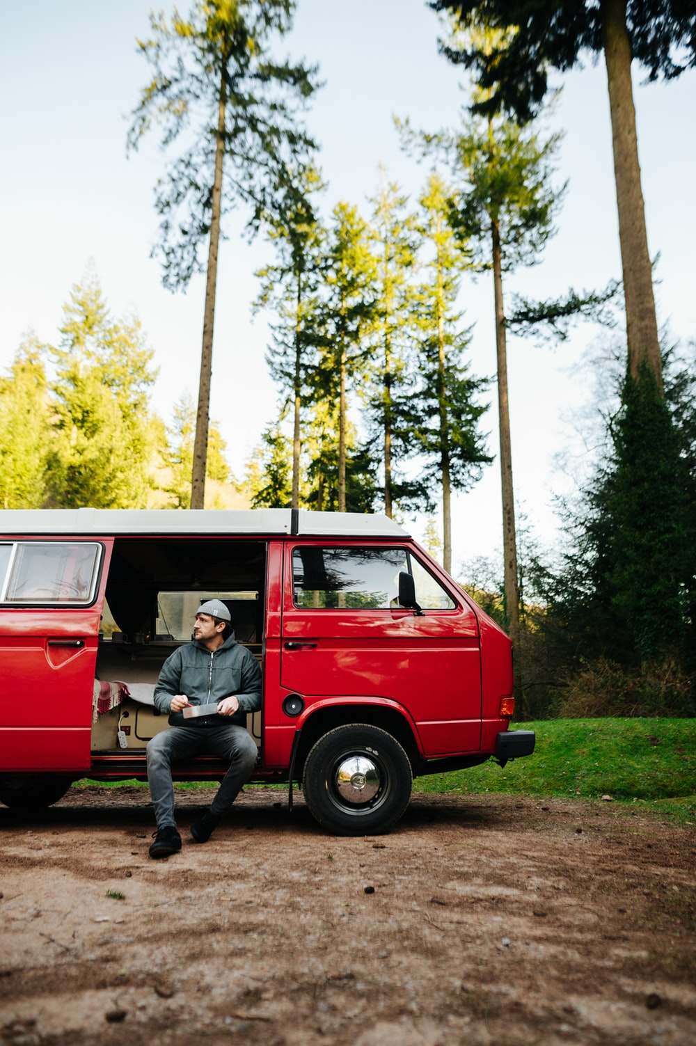 man in blue shirt sitting on red van