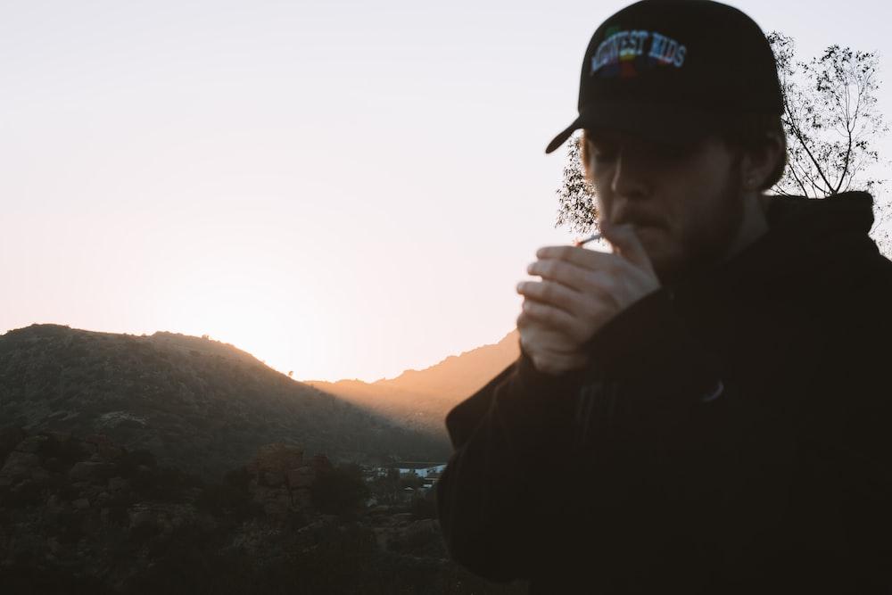 man in black jacket wearing black cap