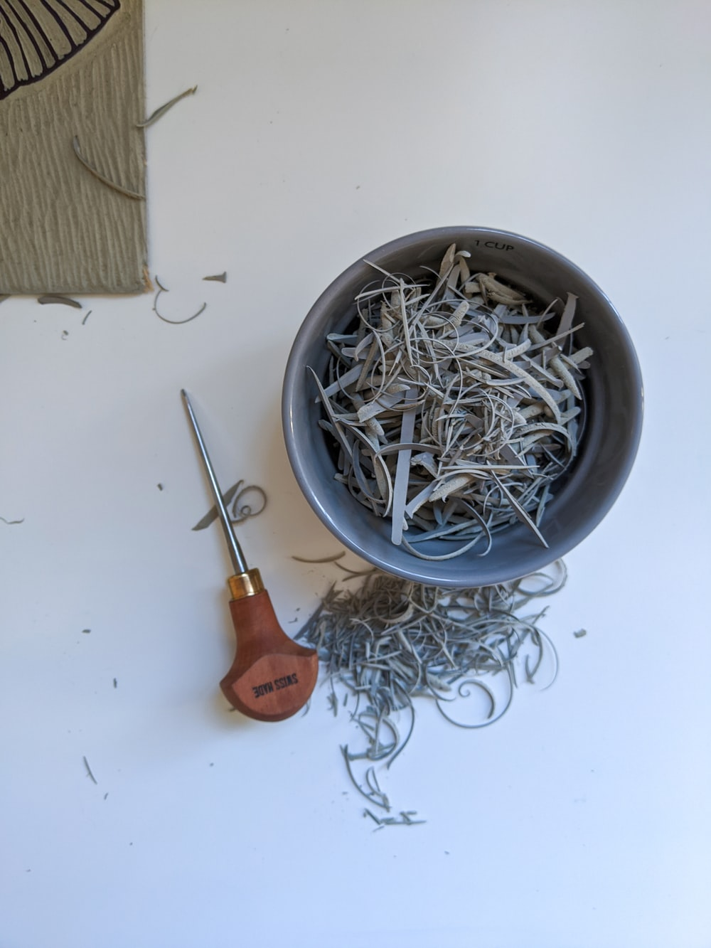 silver and orange handle scissors on gray round bowl