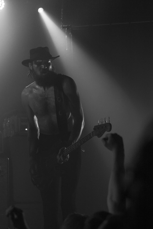 man in black tank top playing guitar