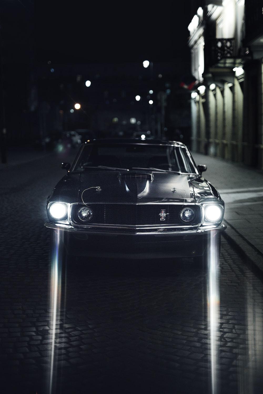 black porsche 911 parked on sidewalk during night time