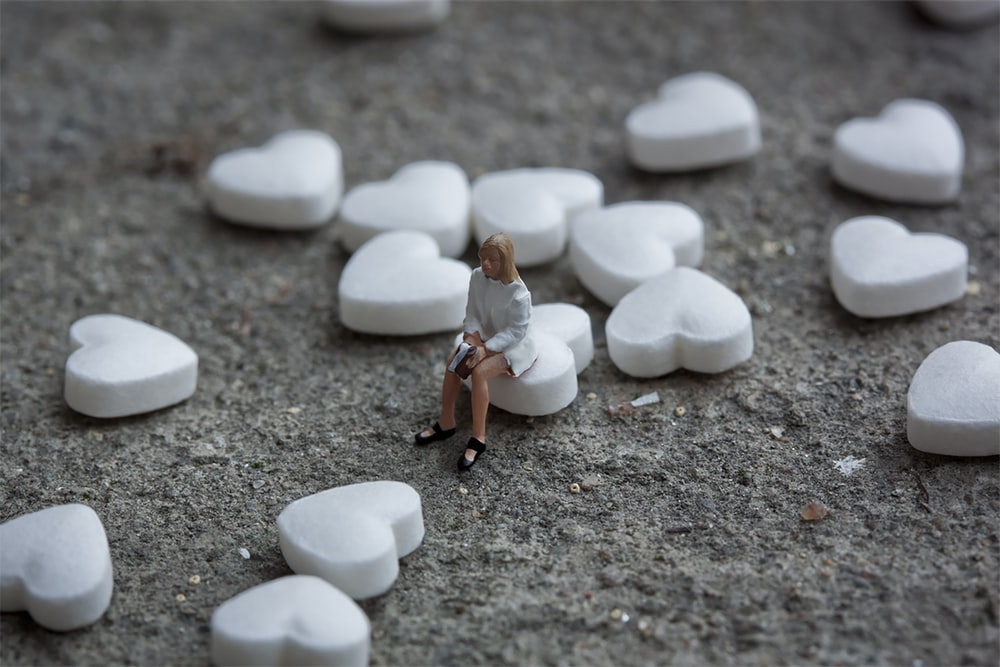 woman in white shirt and brown pants standing on white pebbles