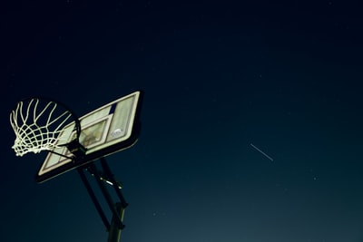 black and white basketball hoop under starry night iss teams background