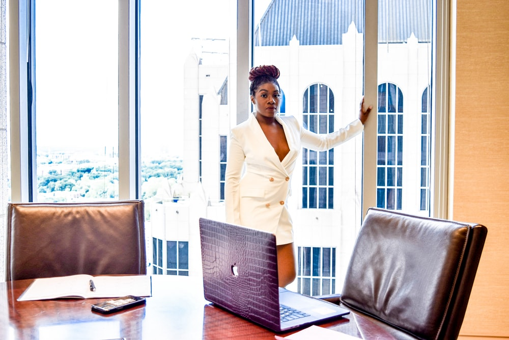 woman in white blazer standing near window