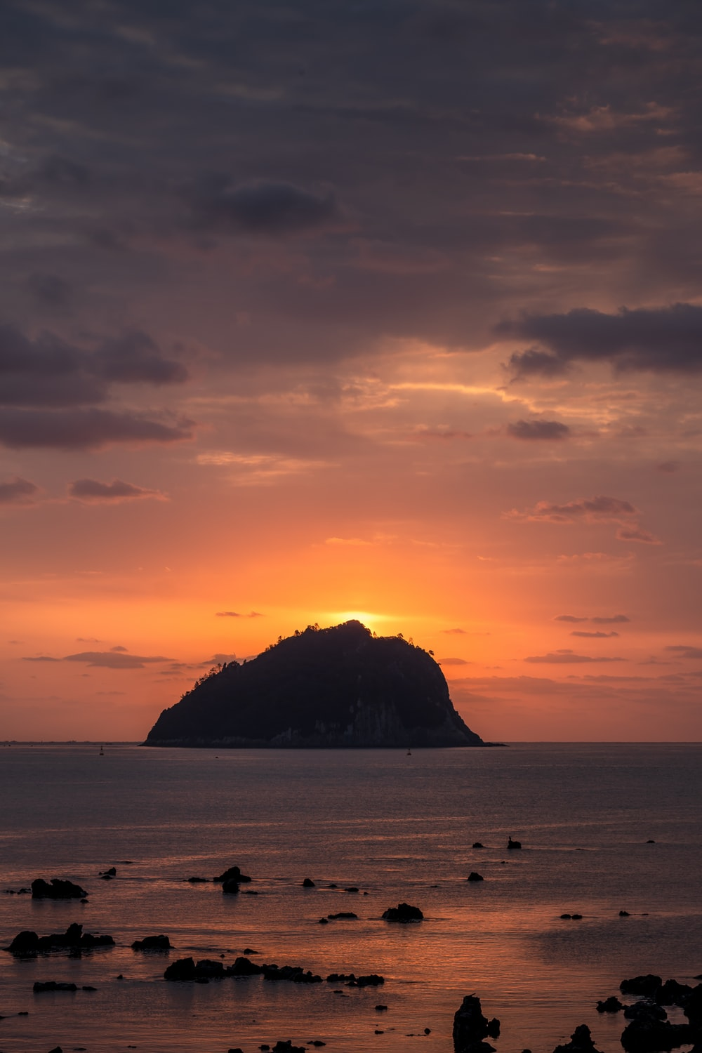 silhouette of island on sea during sunset