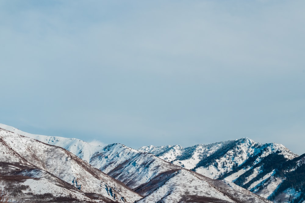 snow covered mountains under white sky during daytime