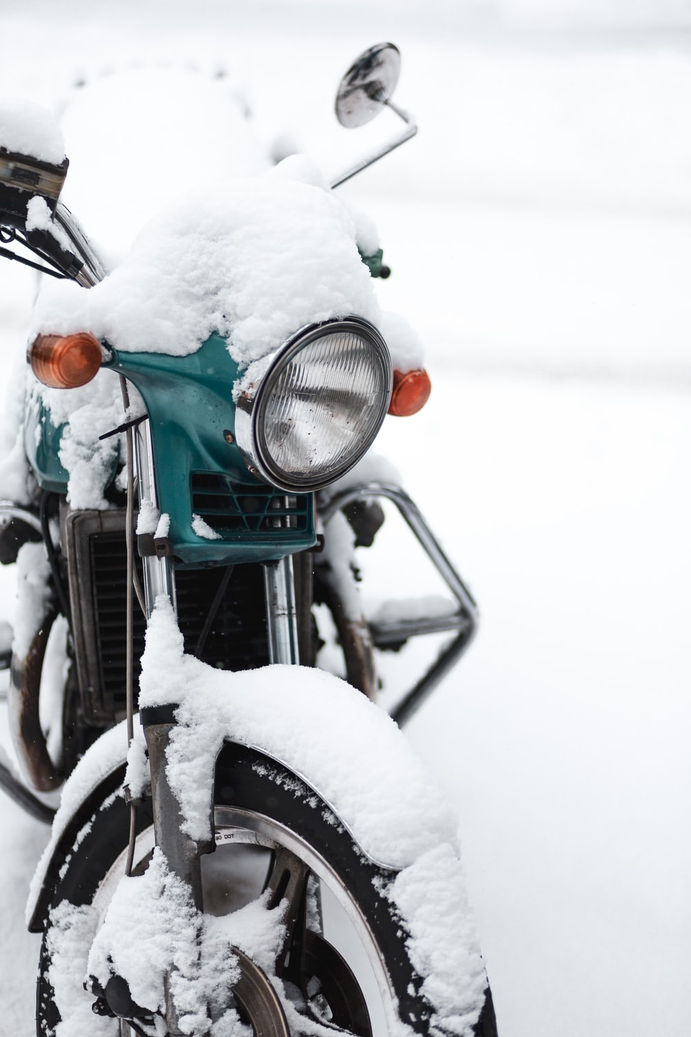 green and black motorcycle on snow covered ground during daytime