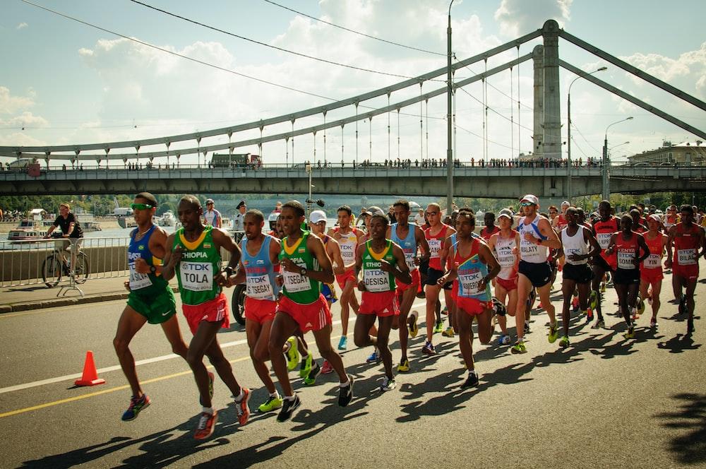 group of people running on gray concrete bridge during daytime