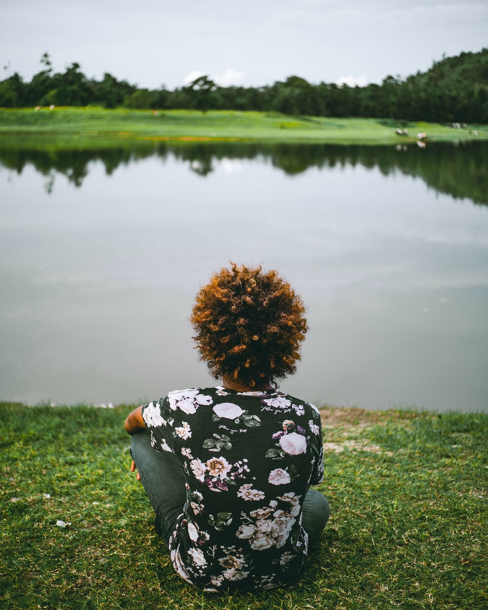 woman in black and white floral long sleeve shirt sitting on green grass field near lake