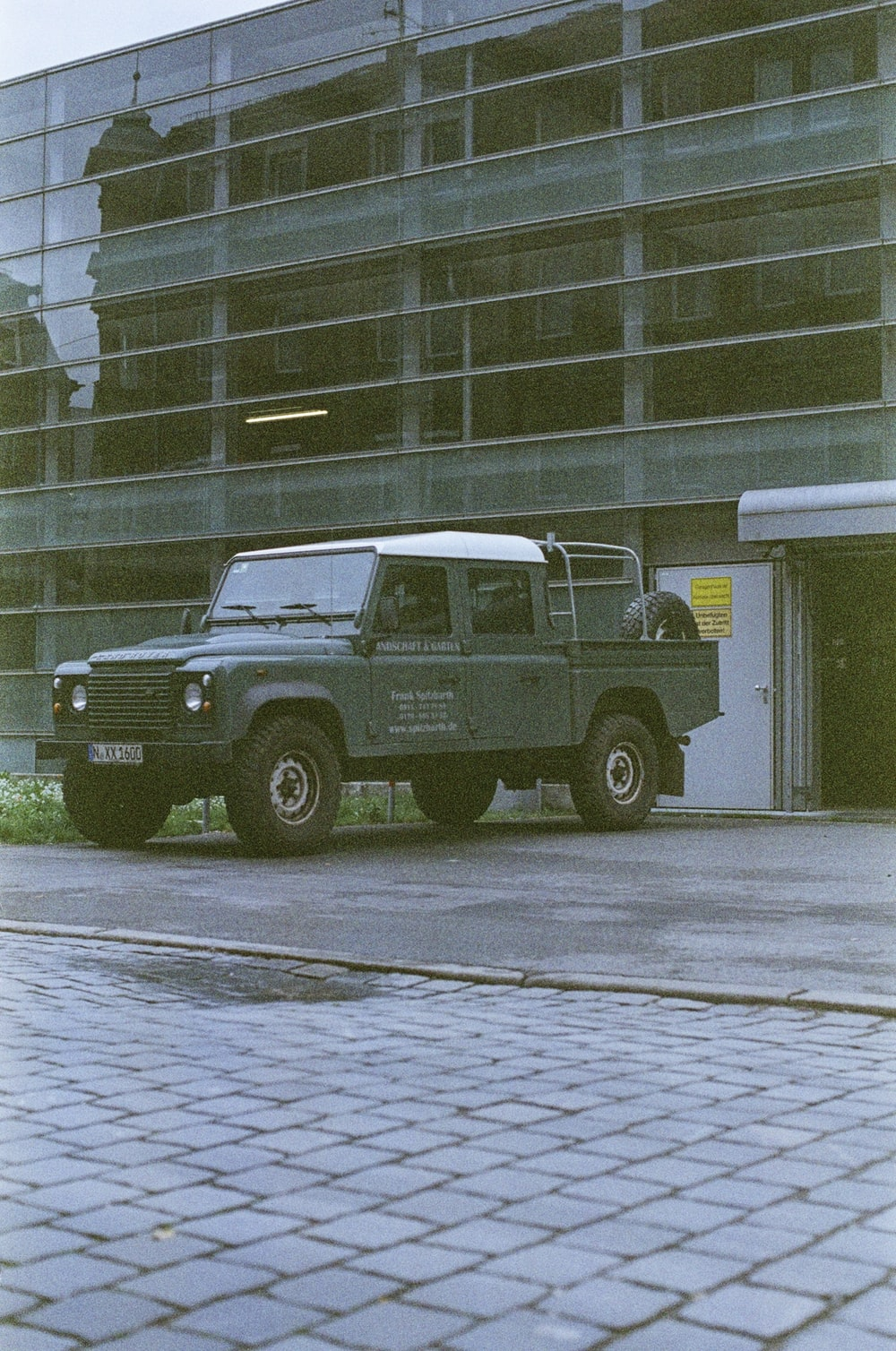 white and black jeep wrangler parked beside brown concrete building during daytime