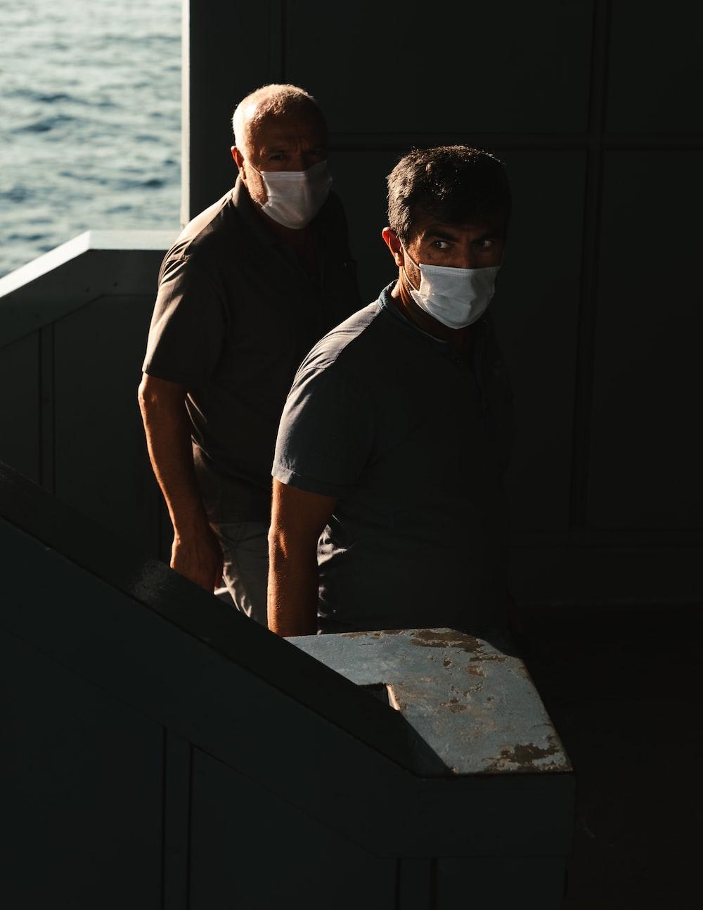 man in black polo shirt standing beside man in black t-shirt