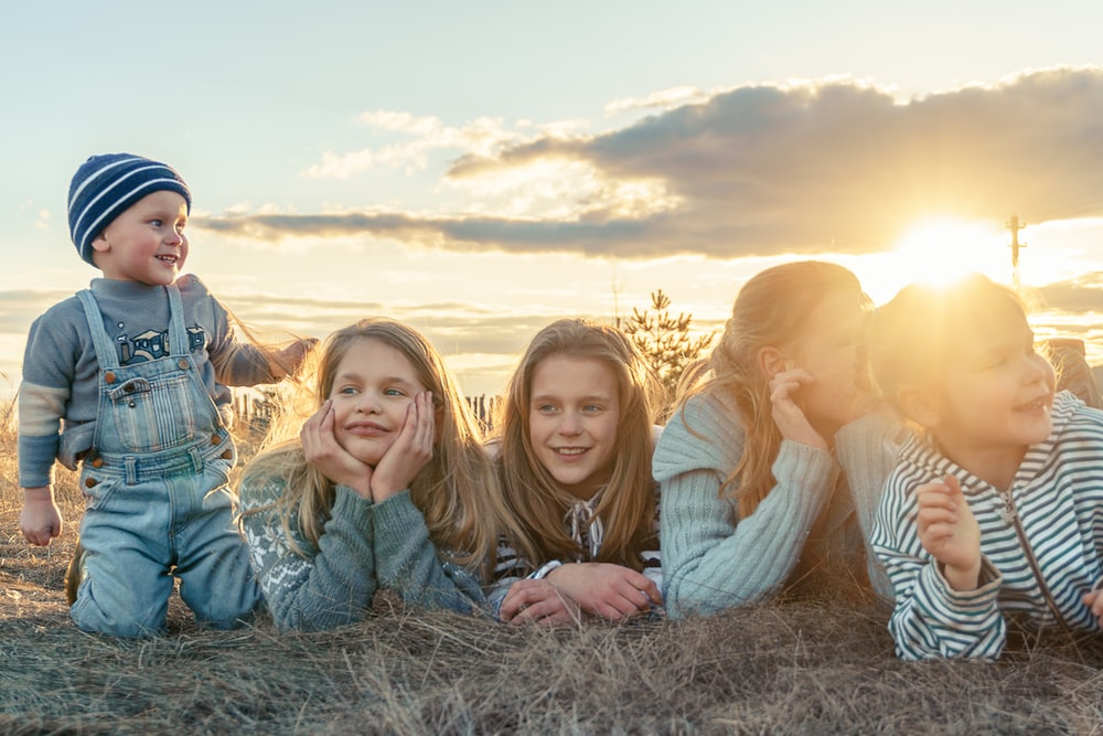 3 women sitting on grass field during sunset