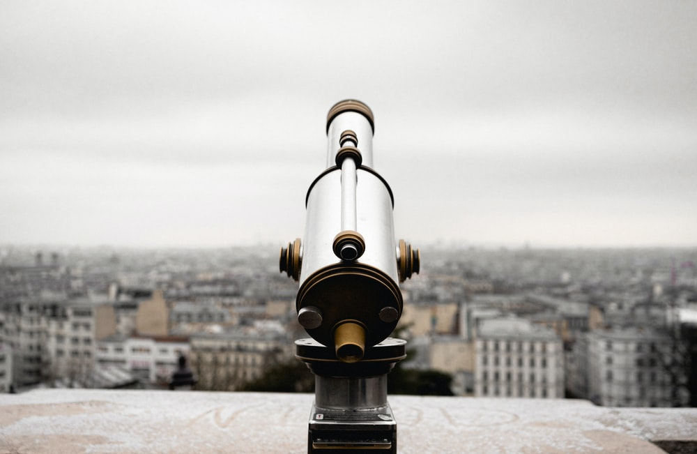 black and gold telescope on top of a building