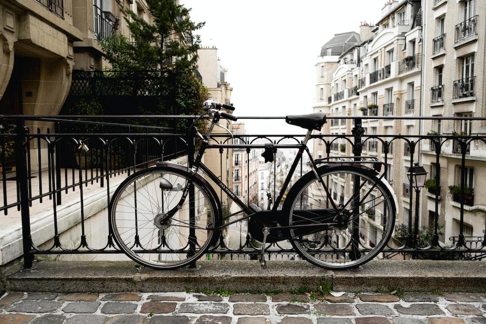 black city bike parked beside black metal fence during daytime