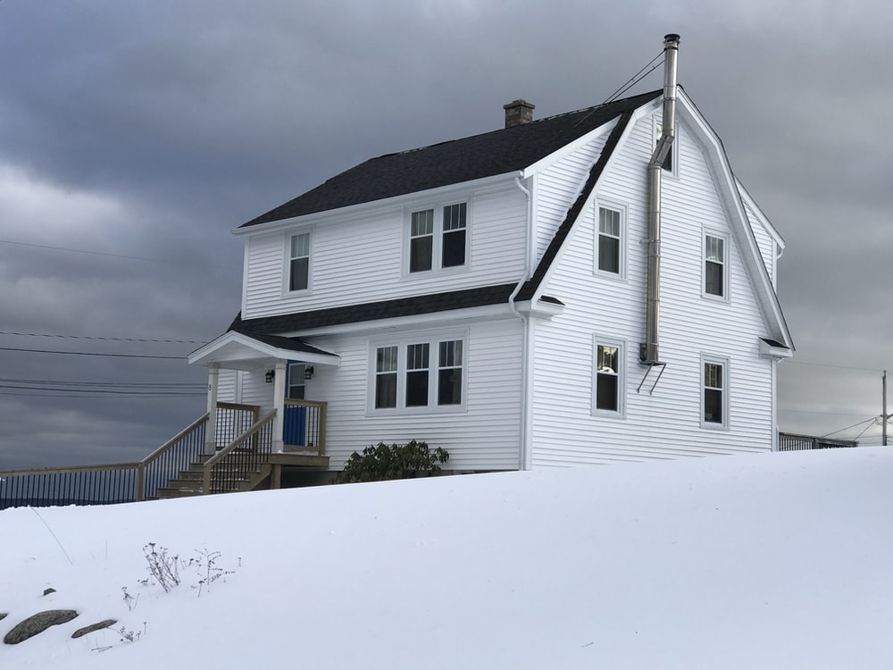 white wooden house on snow covered ground under gray cloudy sky